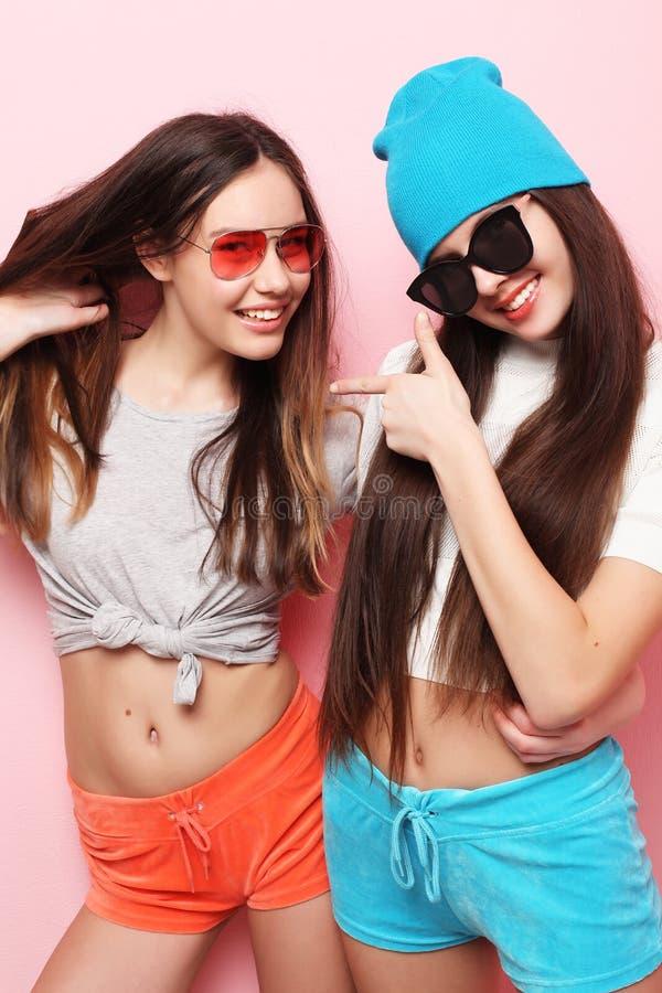 Lyckliga le nätta tonårs- flickor eller vänner som kramar över rosa färger royaltyfria foton