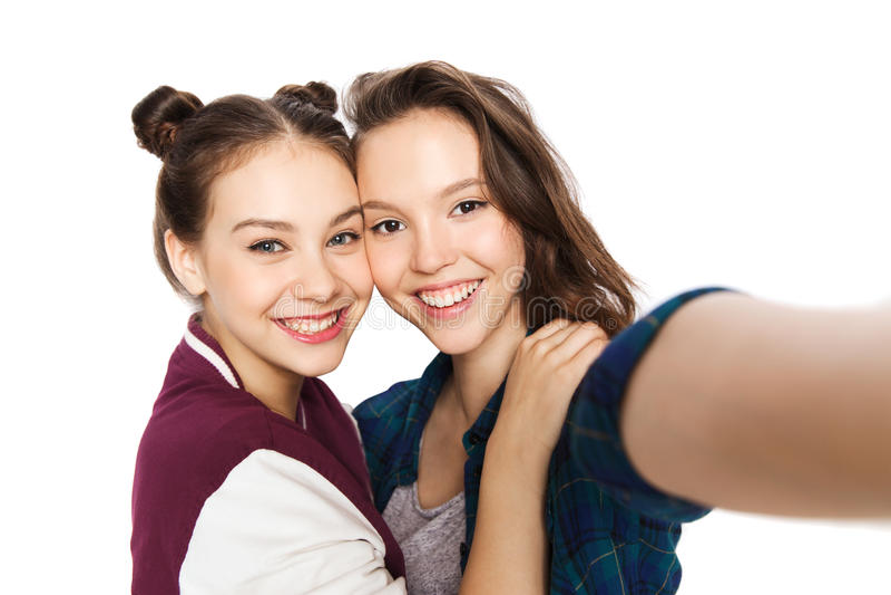 Lyckliga le nätta tonårs- flickor som tar selfie royaltyfri fotografi