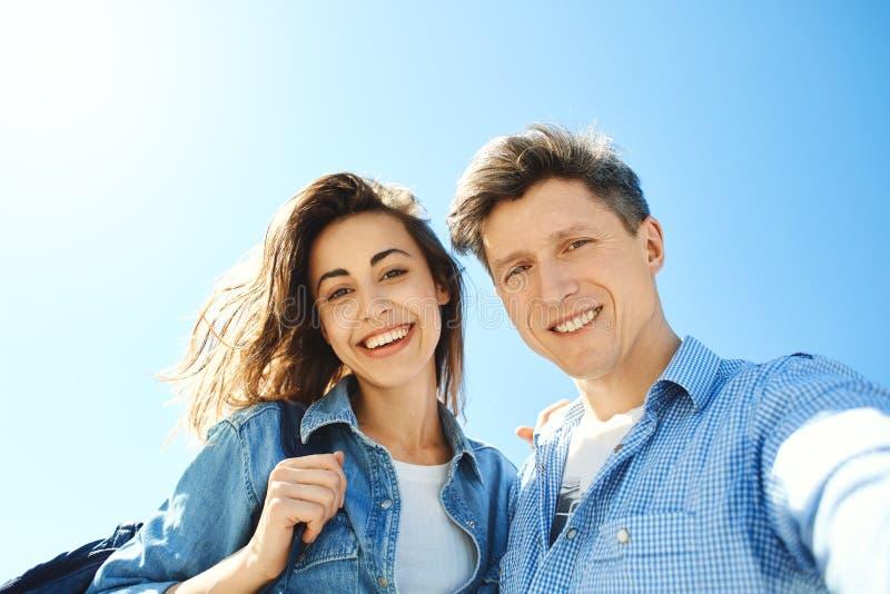 Lyckliga le par, attraktiv man och kvinna som ser i kameran på himmelbakgrunden royaltyfria bilder