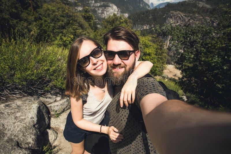 Lyckliga le par av för tagandeselfie för studenter det förälskade självporträttet, medan fotvandra i den Yosemite nationalparken, royaltyfria bilder