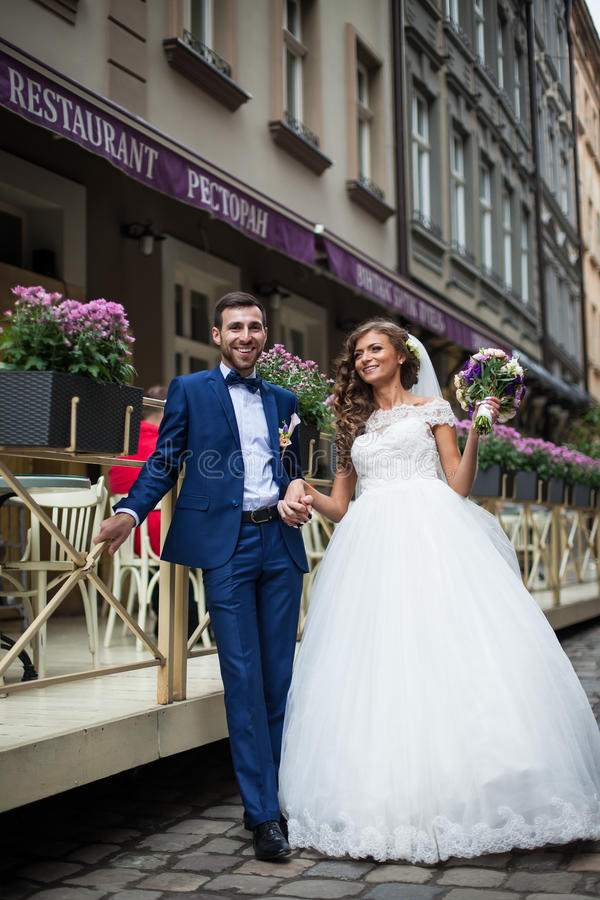 Lyckliga le par av nygifta personer, mannen och kvinnan med buketten arkivbild