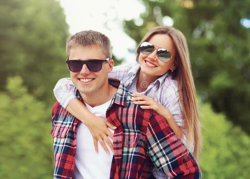 Lyckliga le par för stående i solglasögon som tillsammans kramar, man som ger ridtur på axlarnaritt till kvinnan på suddig sommar royaltyfria bilder