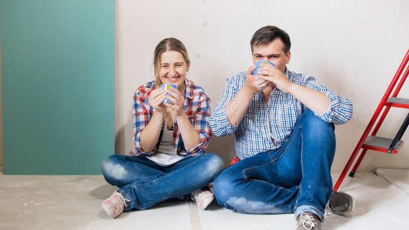 Lyckliga le par kopplar ihop att dricka kaffe i hus under konstruktion royaltyfri bild