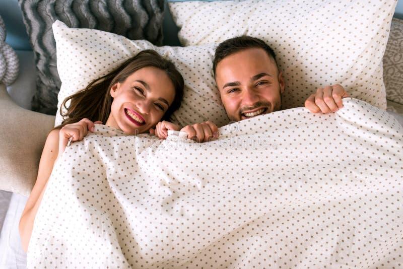 Lyckliga le par som hemma ligger i säng arkivbild