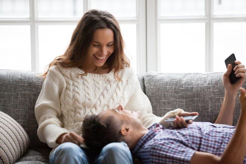 Lyckliga le par som kopplar av på soffan som talar skratta att rymma arkivfoto