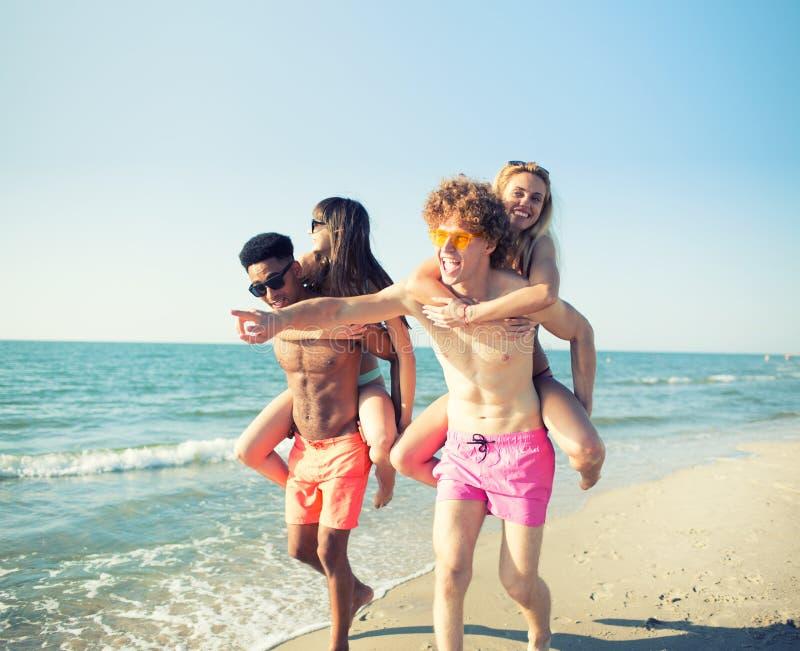 Lyckliga le par som spelar på stranden royaltyfria foton