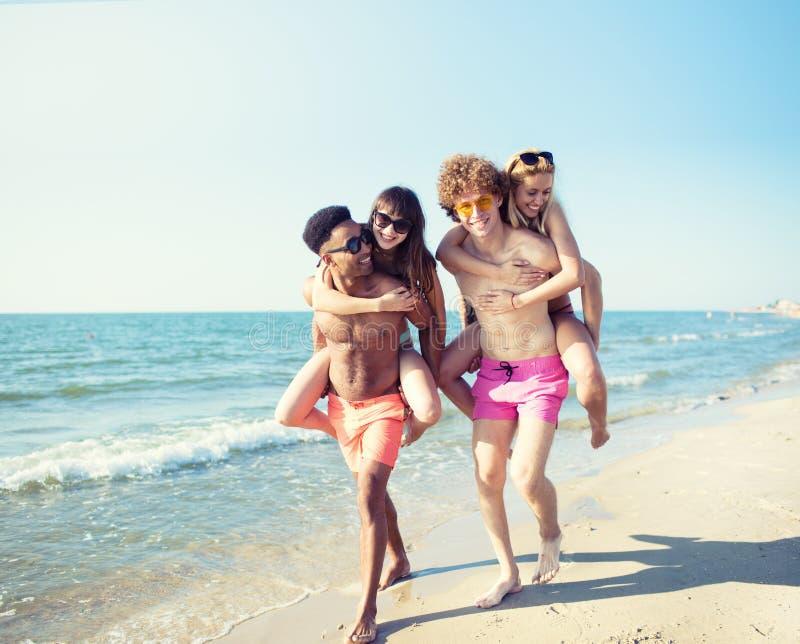 Lyckliga le par som spelar på stranden royaltyfri fotografi