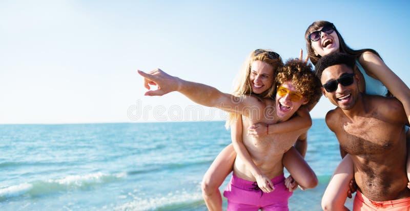 Lyckliga le par som spelar på stranden royaltyfria bilder