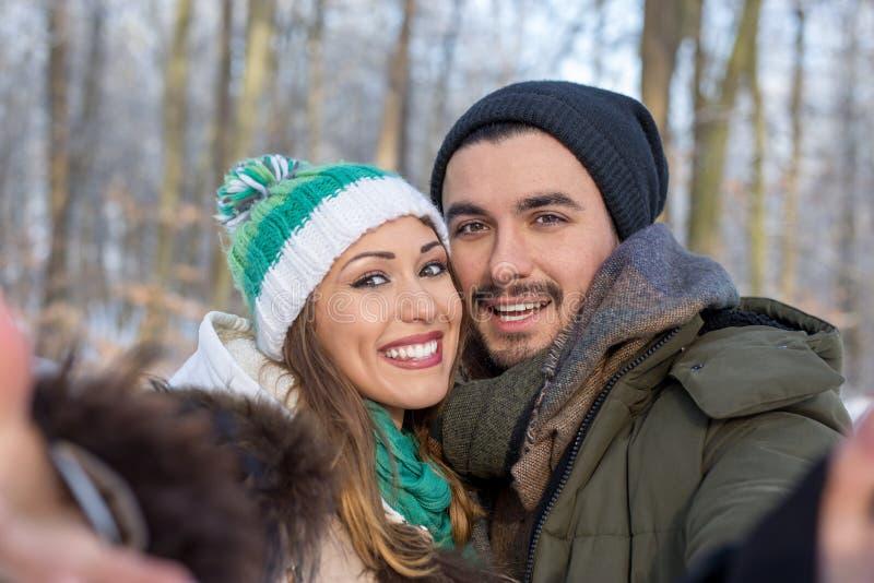 Lyckliga le par som tar en selfie i en vinterskog arkivfoton