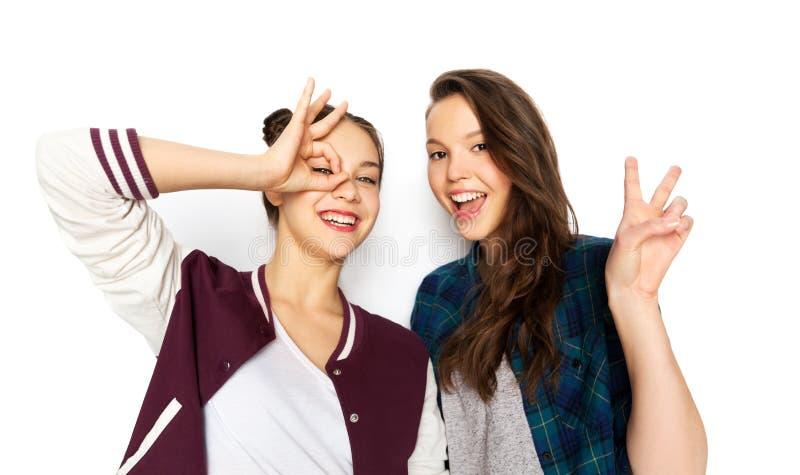 Lyckliga le tonårs- flickor som gör gester royaltyfri foto