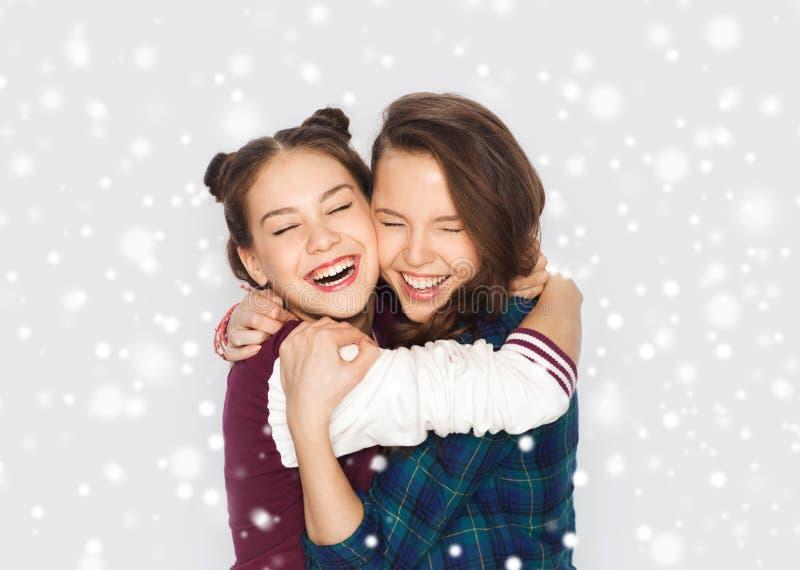 Lyckliga le tonårs- flickor som kramar över snö arkivbilder