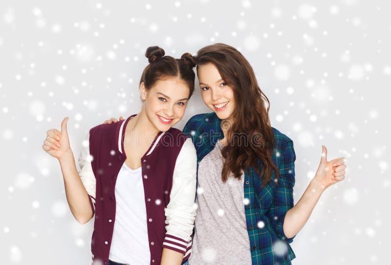 Lyckliga le tonårs- flickor som visar upp tummar royaltyfri foto