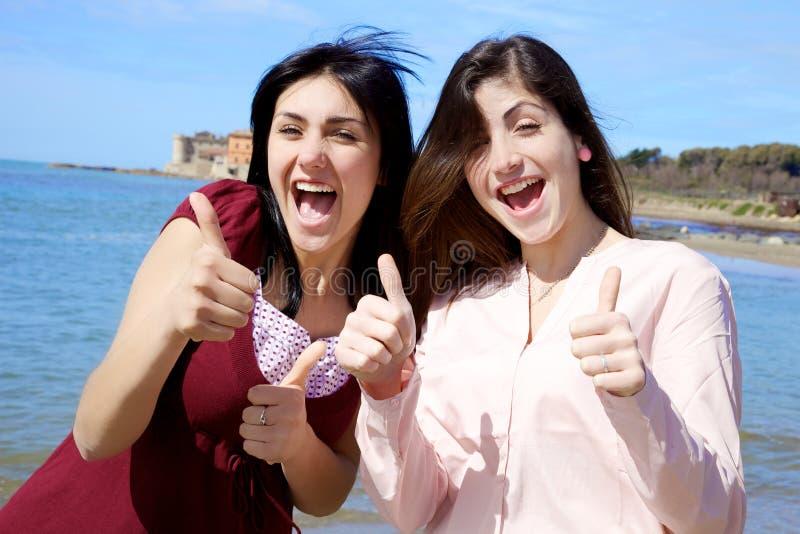 Lyckliga le unga kvinnor framme av havstummen upp royaltyfri foto