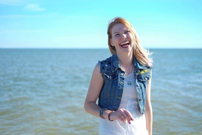 Lyckliga le unga kvinnor på havsbakgrunden fotografering för bildbyråer