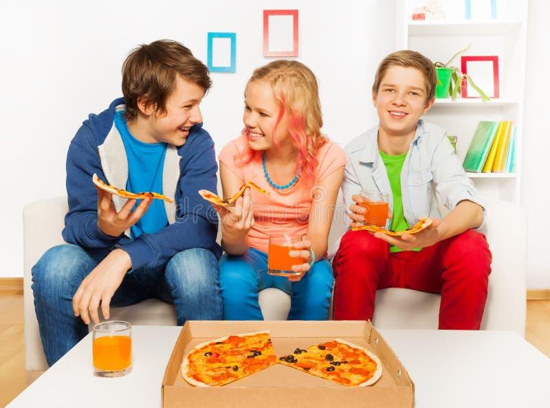 Lyckliga le vänner äter tillsammans pizza hemma royaltyfri fotografi
