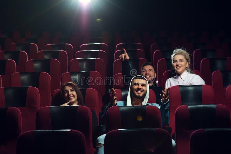 Lyckliga le vänner som håller ögonen på filmen i teater royaltyfri foto