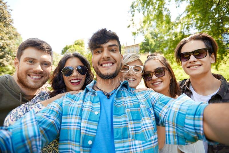 Lyckliga le vänner som tar selfie på sommar, parkerar royaltyfria foton