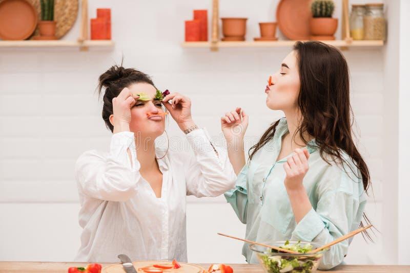 Lyckliga lesbiska par med grönsaken i kök royaltyfria foton