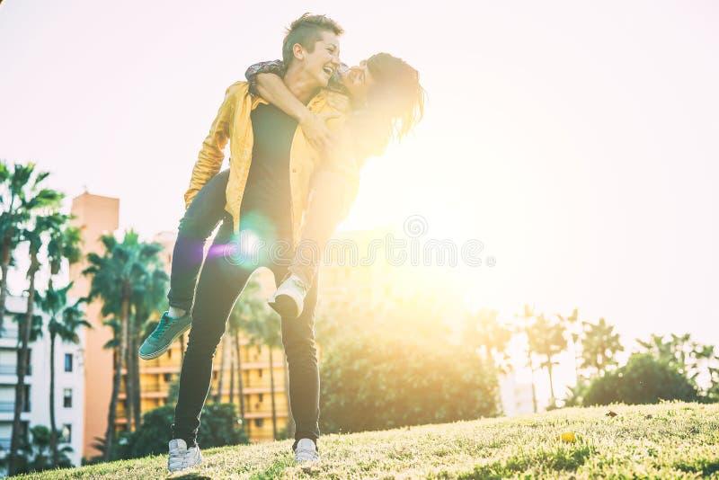 Lyckliga lesbiska par som har gyckel och skrattar på ryggen, medan se sig ögat i parkerar utomhus- arkivbild