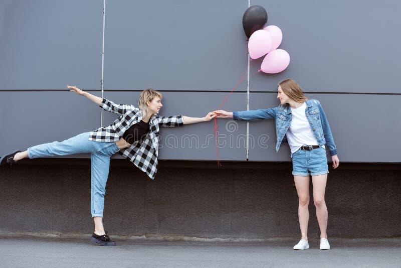 Lyckliga lesbiska parinnehavhänder med luftballonger utomhus royaltyfri foto