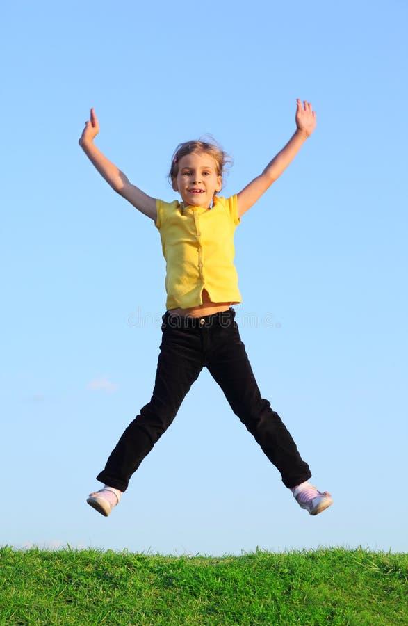 Lyckliga liten flickahopp på gräs royaltyfria foton