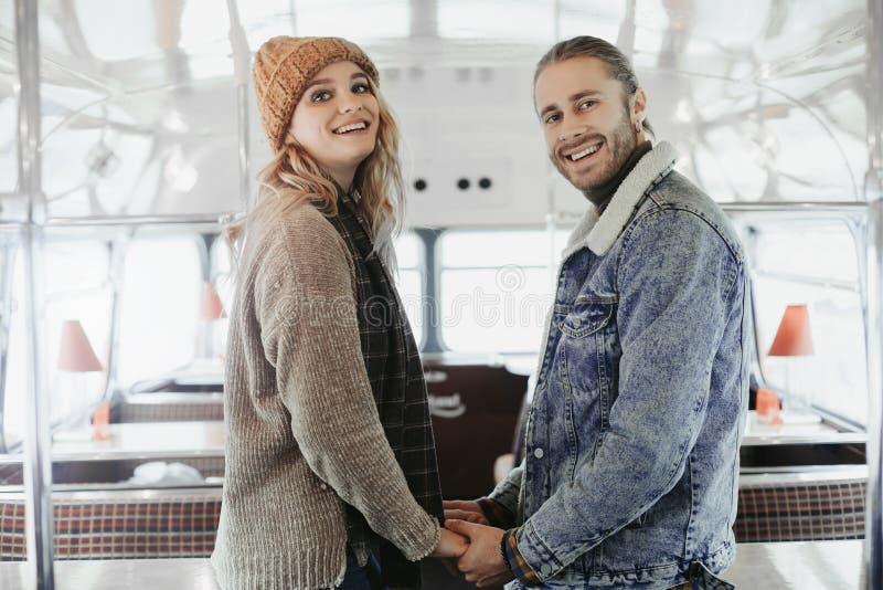 Lyckliga ?lskade par som rymmer h?nder i busskaf? arkivfoto