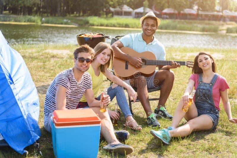 Lyckliga män och kvinnor som gör picknicken med musik royaltyfri foto