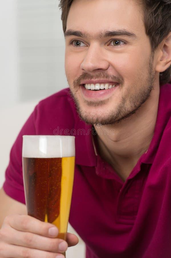 Lyckliga män som dricker öl. Stående av stiligt dricka för unga män arkivbild
