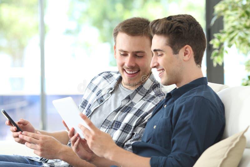 Lyckliga män som kontrollerar online-innehållet på minnestavlan och telefonen royaltyfri bild