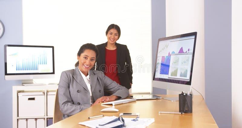 Lyckliga mång--person som tillhör en etnisk minoritet affärskvinnor som i regeringsställning sitter royaltyfri bild