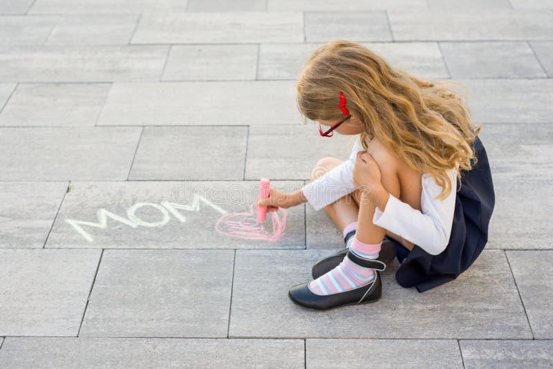 lyckliga mödrar för dag Lite flickaattraktioner för hennes moder en bildöverraskning av färgpennor på asfalten Förälskelsemamma royaltyfri foto