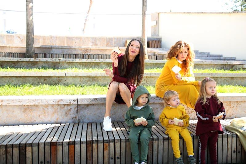 lyckliga mödrar med barn i parkerar i familj-stil kläder royaltyfria bilder