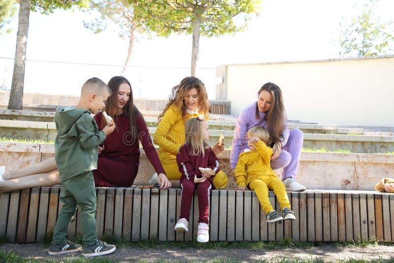 Lyckliga mödrar med barn i trendig sportswear i familjstil royaltyfri fotografi