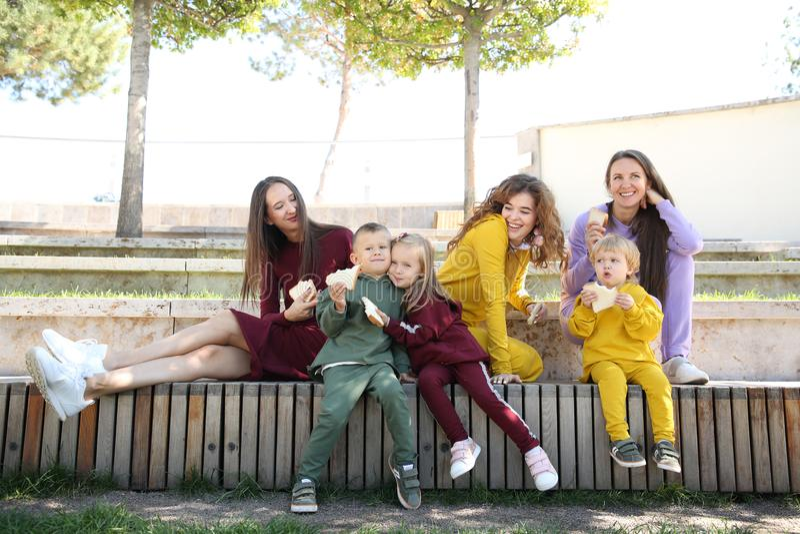 Lyckliga mödrar med barn i trendig sportswear i familjstil royaltyfria foton