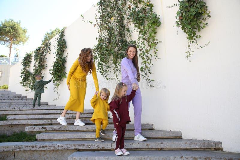 Lyckliga mödrar med barn i trendig sportswear i familjstil arkivfoton