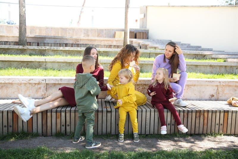 Lyckliga mödrar med barn i trendig sportswear i familjstil royaltyfri foto