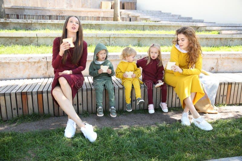Lyckliga mödrar med barn i trendig sportswear i familjstil royaltyfri bild