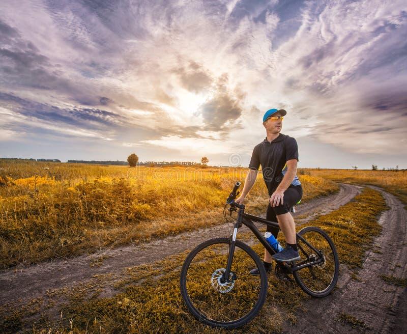 Lyckliga mancyklistritter sätter in vägen på en mountainbike på solnedgången royaltyfria bilder