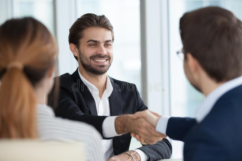 Lyckliga manliga chefer för anställdhandshakingtimme efter bra intervju royaltyfri foto