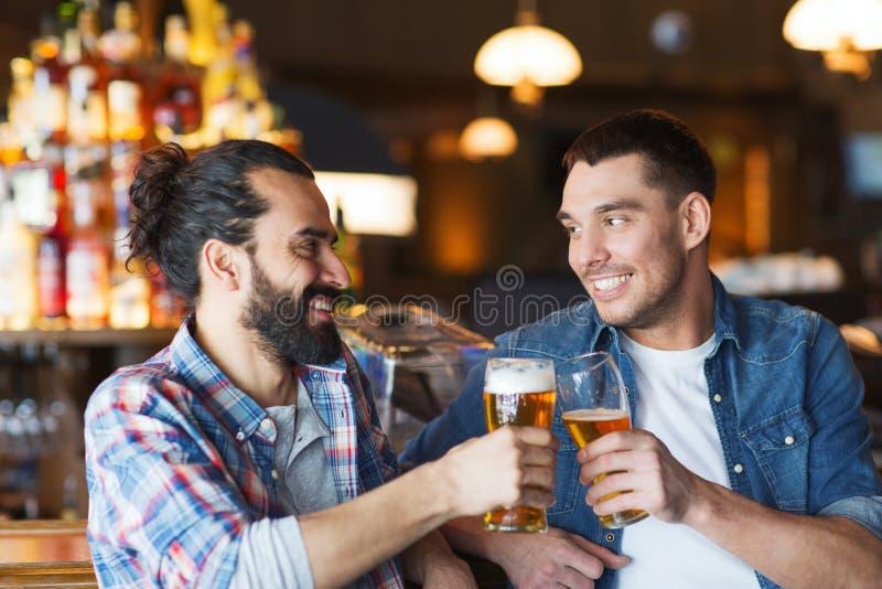Lyckliga manliga vänner som dricker öl på stången eller baren arkivbilder