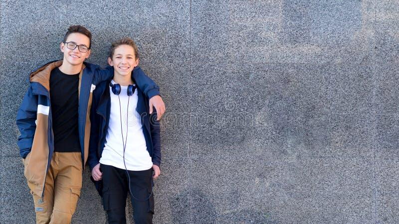 Lyckliga manliga vänner som tillsammans står nära väggen och ser kameran kopiera avst?nd royaltyfri foto