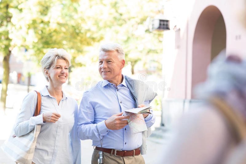 Lyckliga medelåldersa par med översikten som går i stad arkivbild