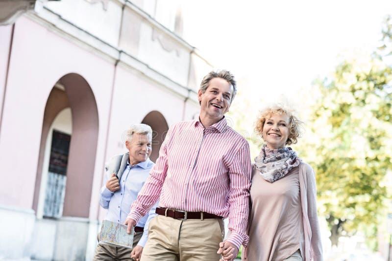 Lyckliga medelåldersa par med översikten som går i stad arkivfoton