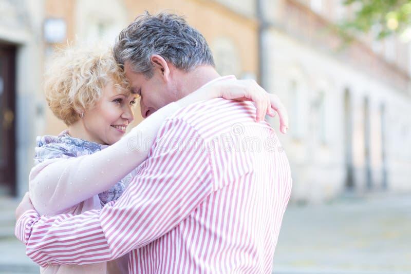 Lyckliga medelåldersa par som omfamnar i stad arkivfoton