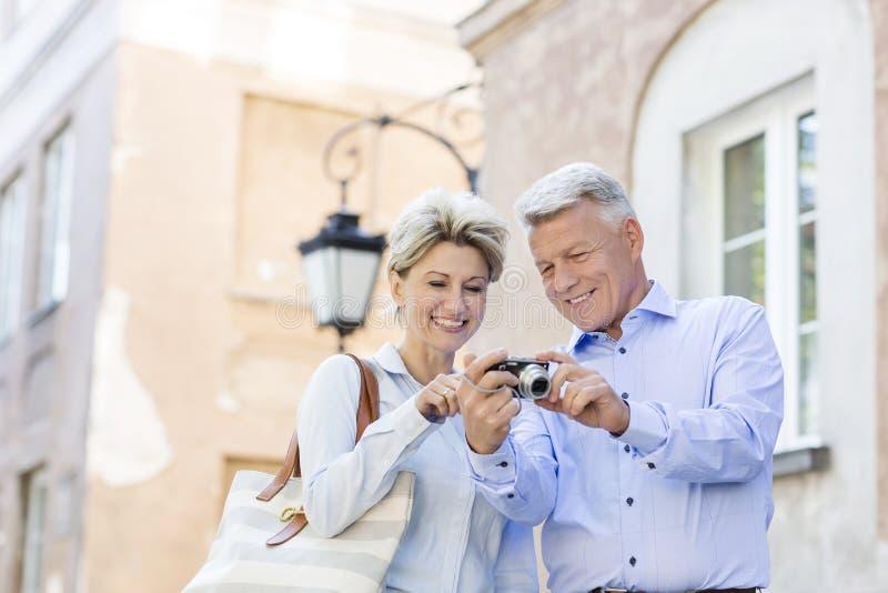 Lyckliga medelåldersa par som ser bilder på digital kamera i stad fotografering för bildbyråer