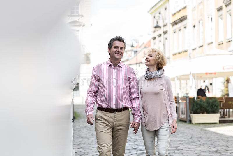 Lyckliga medelåldersa par som talar, medan gå i stad arkivbilder