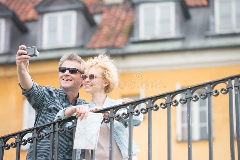 Lyckliga medelåldersa par som tar selfie mot byggnad royaltyfri foto