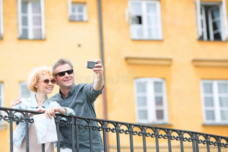 Lyckliga medelåldersa par som tar selfie till och med kamera mot byggnad royaltyfria foton