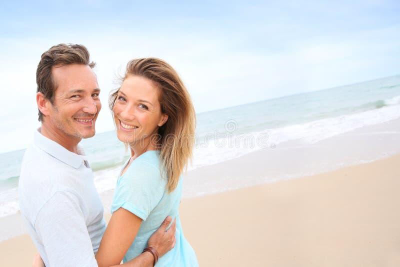 Lyckliga medelåldersa par som tycker om på stranden arkivfoto