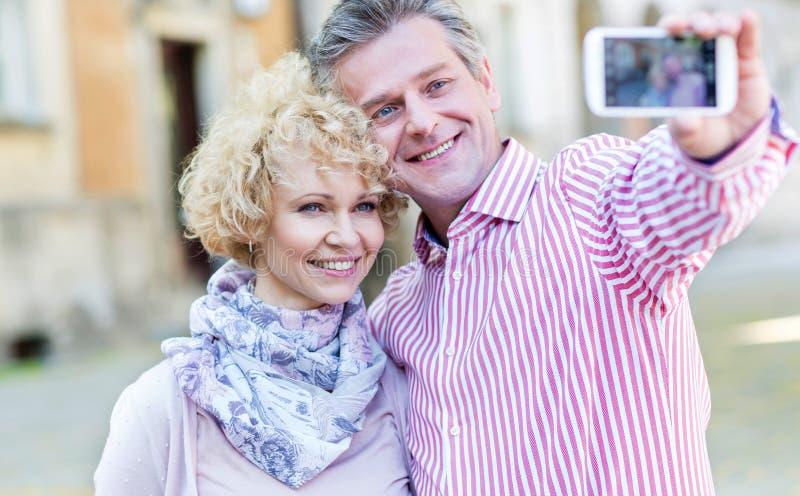 Lyckliga medelåldersa par som utomhus tar selfie till och med den smarta telefonen royaltyfri foto